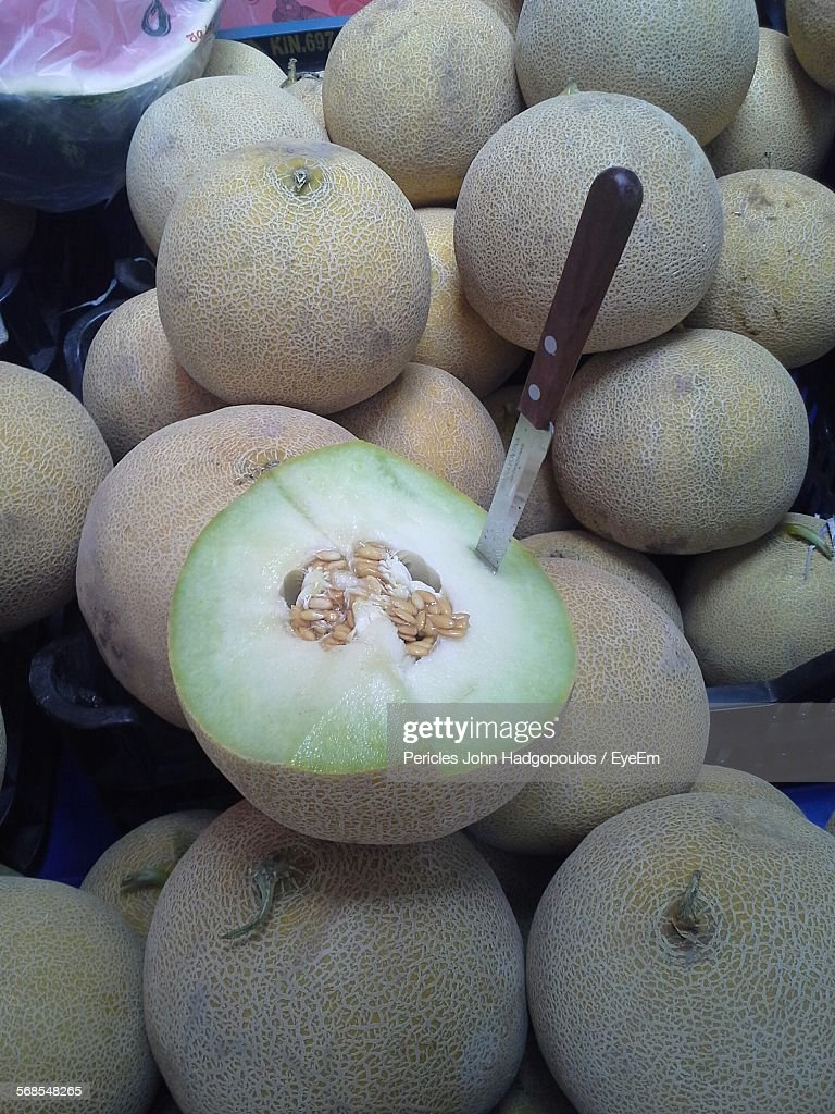 Close-Up Of Fresh Muskmelons With Knife In Market : Stock Photo