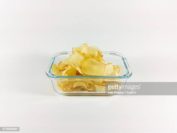 Close-Up Of Fresh Potato Chips In Glass Bowl Against White Background