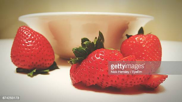 Close-Up Of Fresh Strawberries By Bowl On Table
