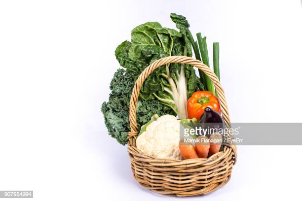 Close-Up Of Fresh Vegetables In Basket Against White Background