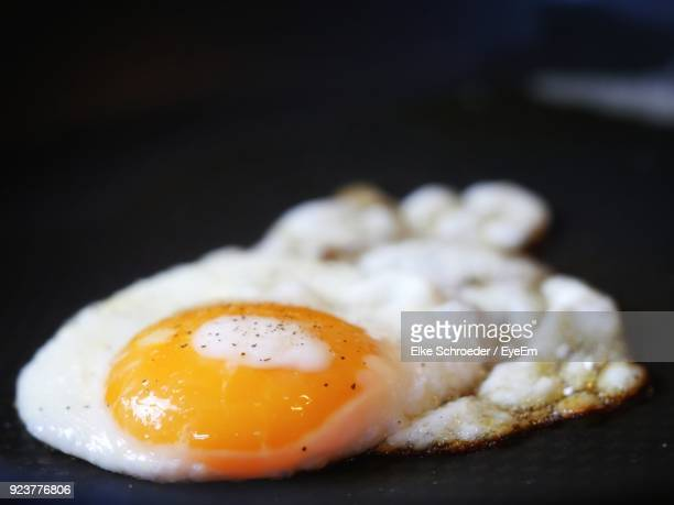 close-up of fried egg over black background - fried eggs stock pictures, royalty-free photos & images