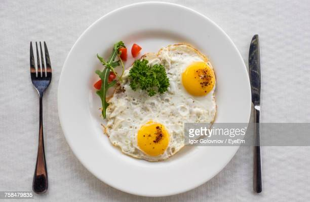 close-up of fried egg served with parsley in plate on table - igor golovniov stock pictures, royalty-free photos & images