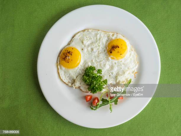 close-up of fried egg served with parsley in plate on table - fried eggs stock pictures, royalty-free photos & images
