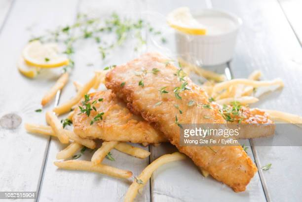 close-up of fried fish and french fries on table - fried stock pictures, royalty-free photos & images