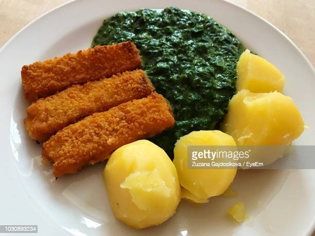 Close-Up Of Fried Fish With Boiled Potato And Spinach Gravy In Plate