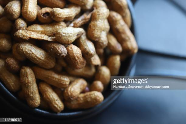 closeup of fried peanuts on dark background - nanette j stevenson stock photos and pictures