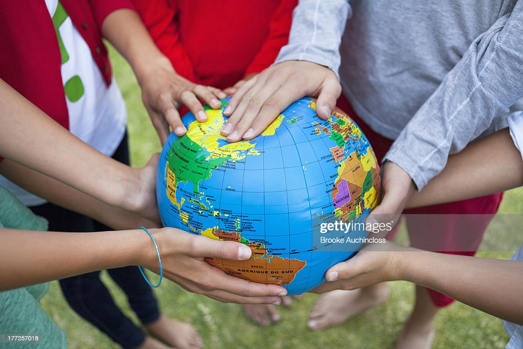 Close-up of friends holding a globe : Stock Photo