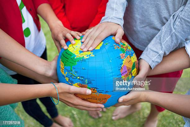 close-up of friends holding a globe - world kindness day fotografías e imágenes de stock