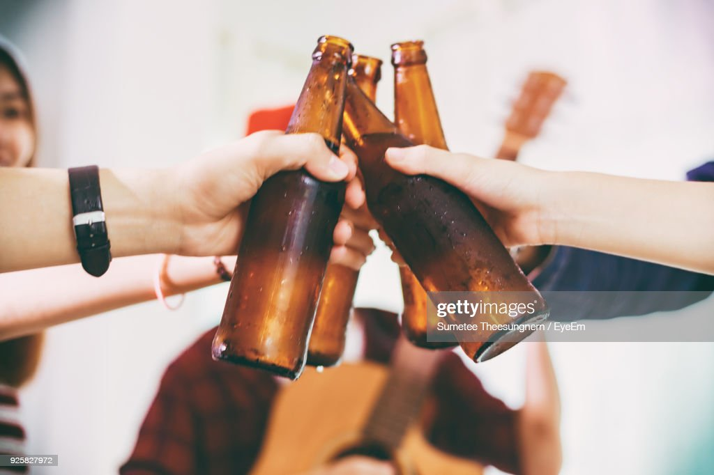 Close-Up Of Friends Toasting Beer Bottles : Stock Photo
