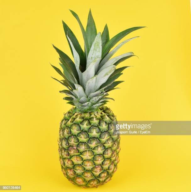 close-up of fruit against yellow background - pineapple stock pictures, royalty-free photos & images
