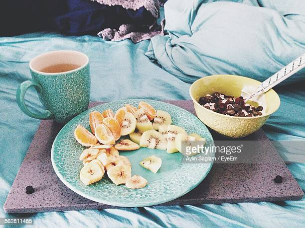Close-Up Of Fruit Salad With Coffee On Bed
