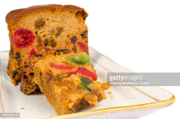 close-up of fruitcake in plate against white background - fruit cake stock pictures, royalty-free photos & images