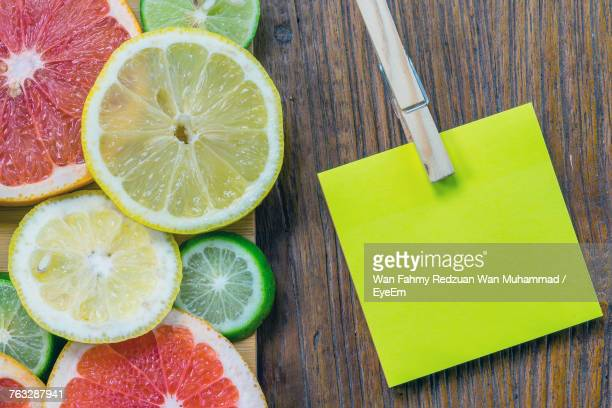 Close-Up Of Fruits By Adhesive Note On Wooden Table