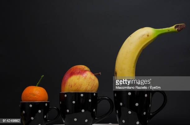 Close-Up Of Fruits In Cups Against Black Background