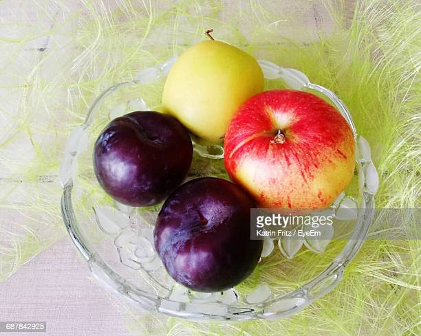 Close-Up Of Fruits In Glass Plate On Artificial Feathers On Table