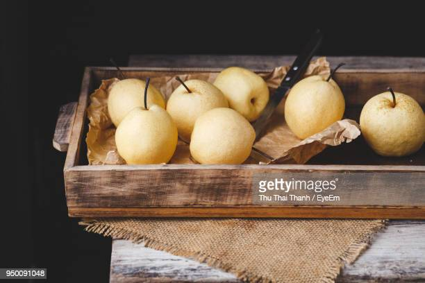 Close-Up Of Fruits In Wooden Box Against Black Background