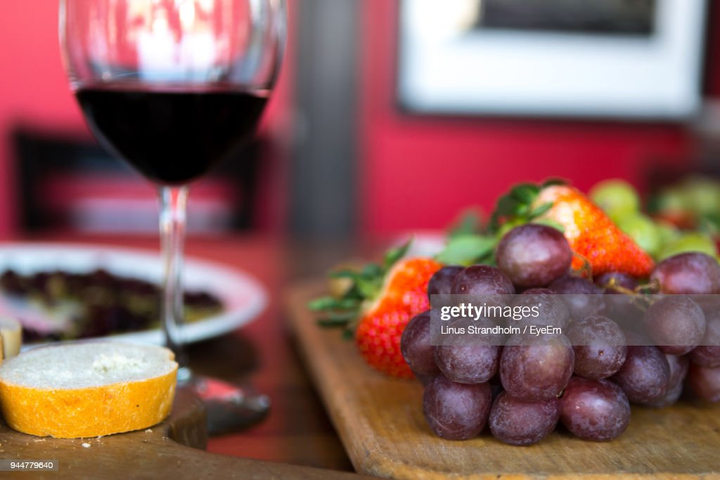Close-Up Of Fruits On Cutting Board By Wine At Table : Stock Photo