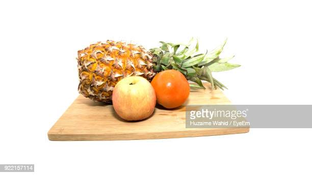 Close-Up Of Fruits On Cutting Board Over White Background