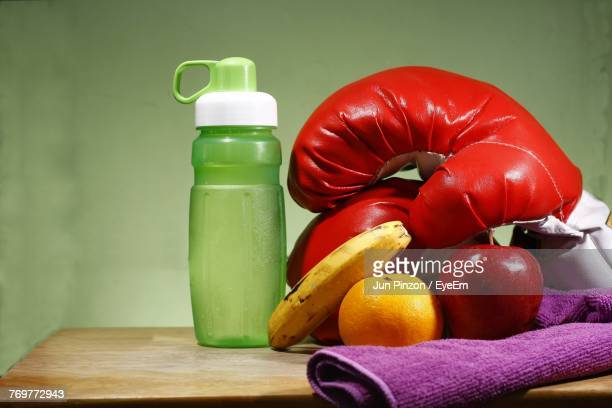 Close-Up Of Fruits With Boxing Gloves And Water Bottle On Table Against Green Background