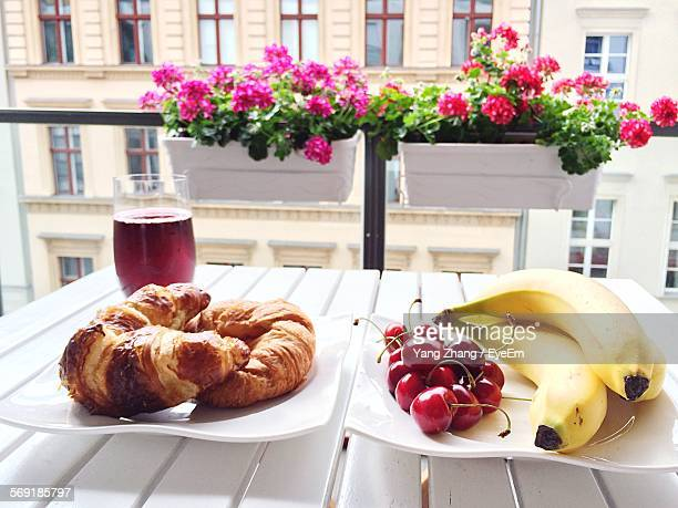 Close-up of fruits with bread and drink served on table at home