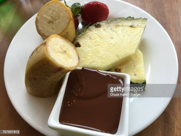 Close-Up Of Fruits With Chocolate Sauce In Plate On Table