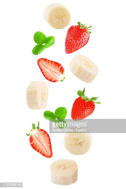 close-up of fruits with herbs over white background - バナナ ストックフォトと画像