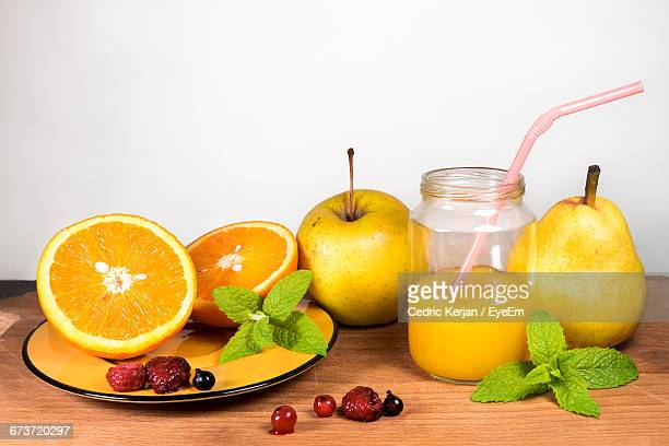 Close-Up Of Fruits With Juice And Mint Leaves On Table Against Wall