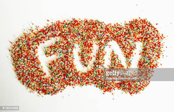 Close-Up Of Fun Text Made With Colorful Sprinkles Over White Background