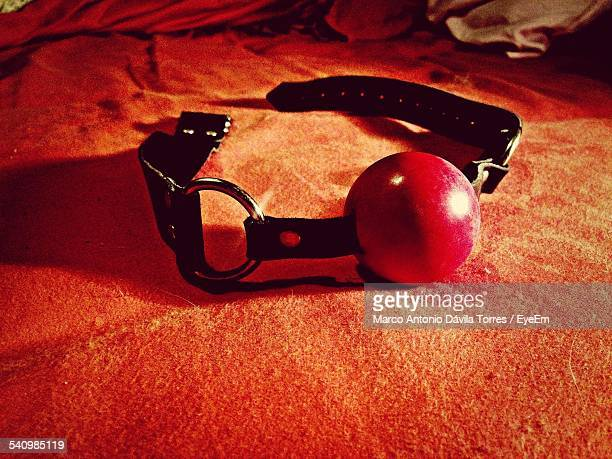 close-up of gag ball on bed at home - sex toy stock photos and pictures