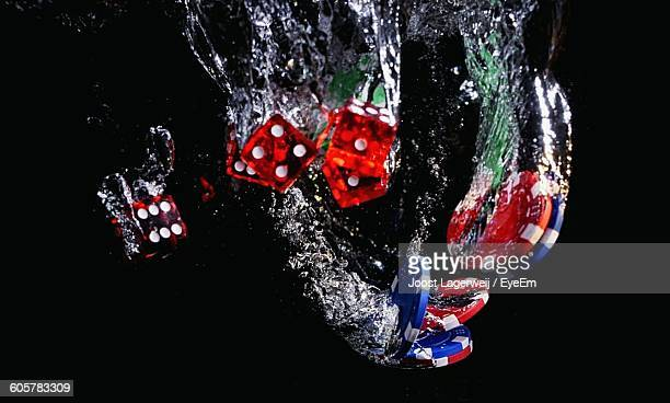 Close-Up Of Gambling Chips And Dices In Water