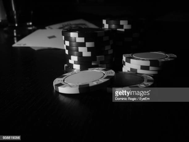 close-up of gambling chips on table in darkroom - gambling table stock pictures, royalty-free photos & images