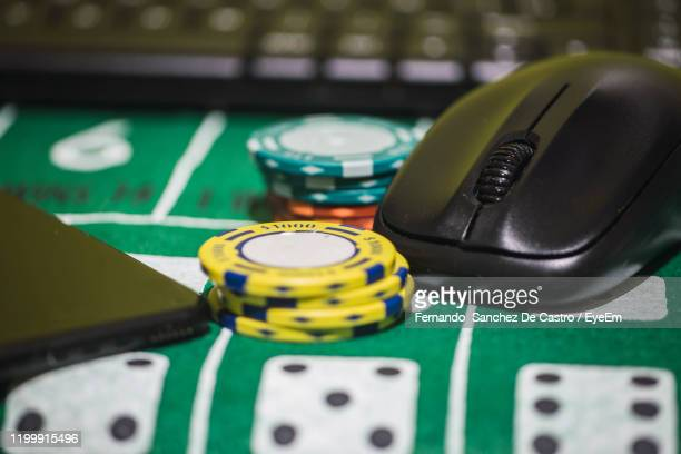 close-up of gambling chips with computer equipment on table - gambling table stock pictures, royalty-free photos & images