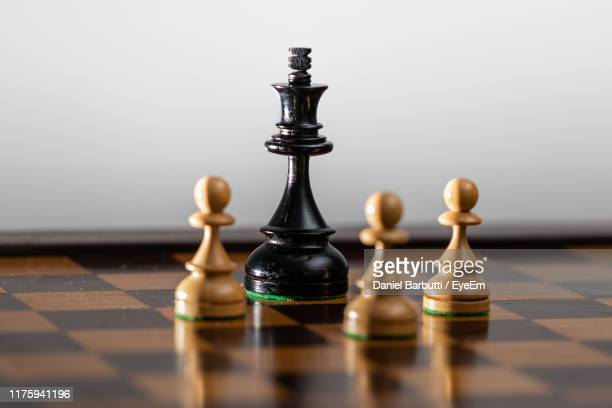 close-up of game pieces on chess board against gray background - king stock pictures, royalty-free photos & images