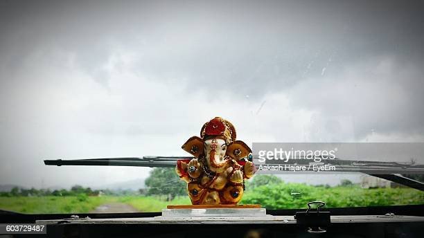 Close-Up Of Ganesha On Car Dashboard Against Sky
