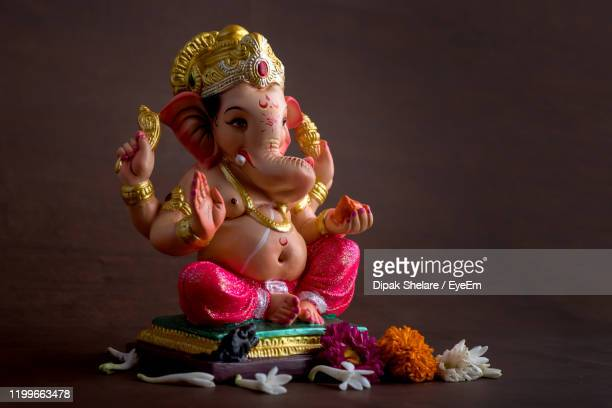 close-up of ganesha statue against colored background - ganesha stock pictures, royalty-free photos & images