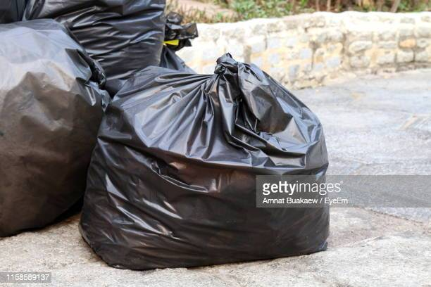 close-up of garbage bags on road - bin bag stock pictures, royalty-free photos & images