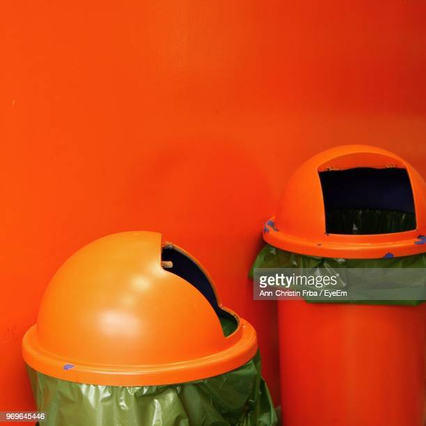 Close-Up Of Garbage Can Against Red Wall