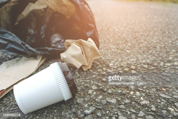close-up of garbage on road - disposable stock photos and pictures