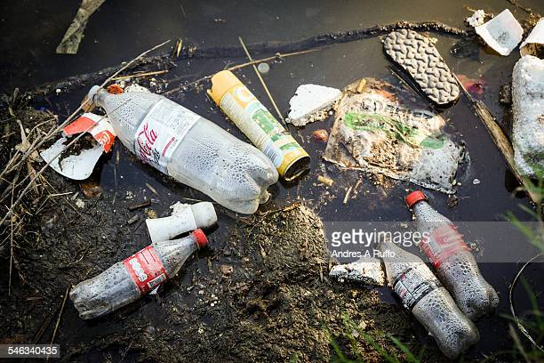 Closeup of garbage on the banks of river first in the center of the city of Córdoba Argentina on Sunday March 29 2015