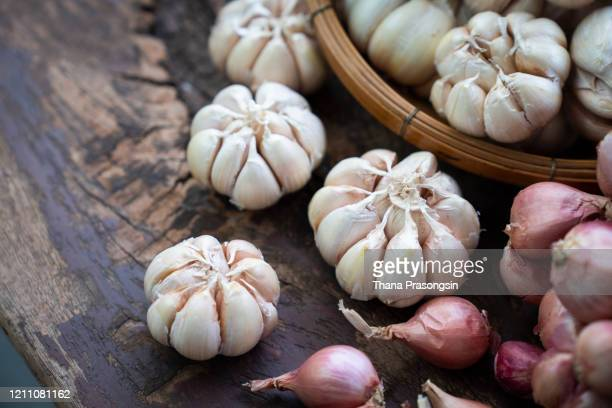 close-up of garlic and onions in wicker basket - garlic stock pictures, royalty-free photos & images