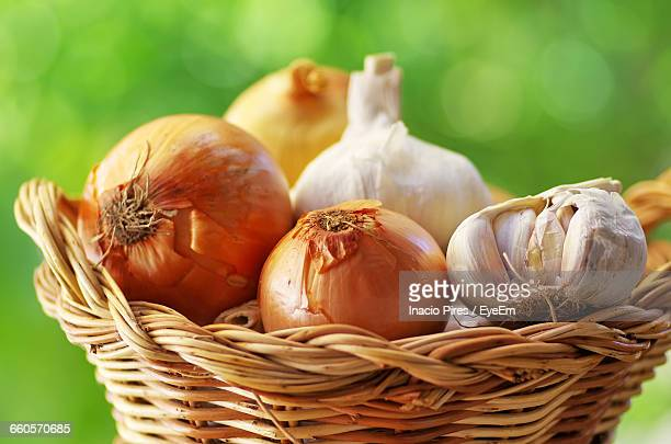 close-up of garlic and onions in wicker basket - cebolla fotografías e imágenes de stock