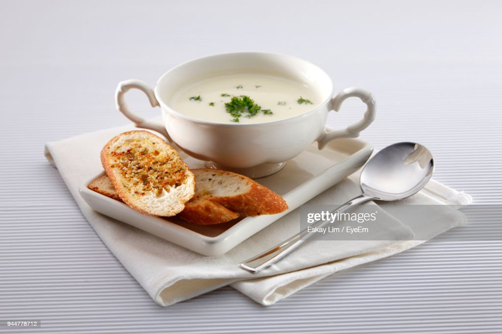Close-Up Of Garlic Breads And Soup On Table : Stock Photo