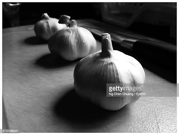 close-up of garlic bulbs and knife on the table - black and white vegetables stock photos and pictures
