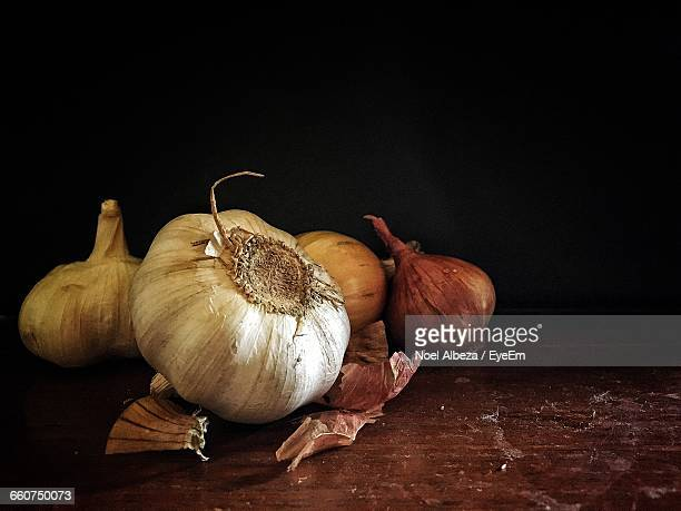 Close-Up Of Garlic Bulbs And Onion On Table Against Black Background