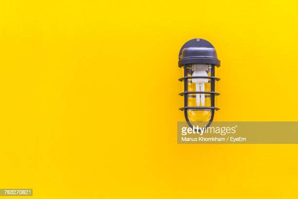 close-up of gas light on yellow wall - electric lamp stock photos and pictures