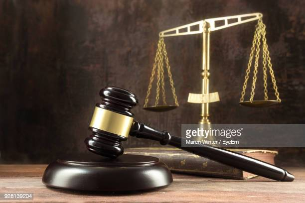 close-up of gavel and weight scale on wooden table - gavel stock pictures, royalty-free photos & images