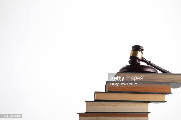 close-up of gavel on stacked books against white background - law stock pictures, royalty-free photos & images