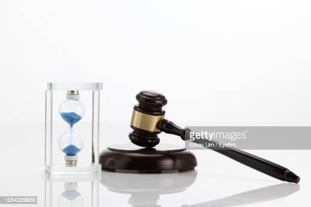 close-up of gavel with hourglass against white background - ora legale foto e immagini stock