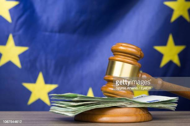 close-up of gavel with paper currency at table against european union flag - european union stock pictures, royalty-free photos & images