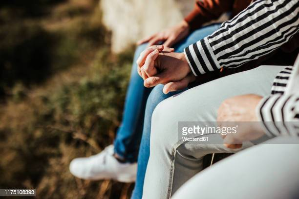 close-up of gay couple holding hands outdoors - hands in her pants - fotografias e filmes do acervo